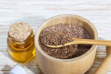 Vegetarian diet healthy vitamin food, cosmetology, personal care, self-eare, traditional alternative medicine, natural vegetable linseed oil in a bottle, flax seeds in a wooden mortar on a table