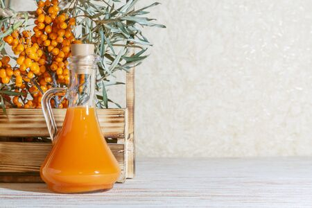 Vegetarian food, healthy nutrition, preserving the harvest of ripe juicy sea-buckthorn, preparing fresh healthy vitamin drink and healing broth. Jug with juice and branches of sea buckthorn on a backg