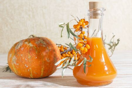 Vegetarian food, healthy nutrition, preserving the harvest of ripe juicy sea-buckthorn and home-made pumpkin, preparing fresh healthy vitamin drink and healing broth. Bottle of juice and branches of o