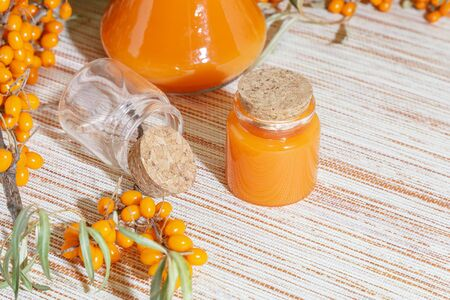 Cosmetology, traditional alternative medicine, herbal medicine, natural sea buckthorn vegetable oil in a glass jar on a table background, healthy juice, branches with a harvest of fresh ripe berries Zdjęcie Seryjne