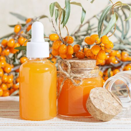 Cosmetology, traditional alternative medicine, herbal medicine, natural sea buckthorn vegetable oil in a glass jar on a table background, healthy juice, branches with a harvest of fresh ripe berries Banque d'images