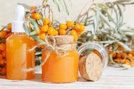 Cosmetology, traditional alternative medicine, herbal medicine, natural sea buckthorn vegetable oil in a glass jar on a table background, healthy juice, branches with a harvest of fresh ripe berries 写真素材