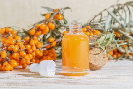 Cosmetology, traditional alternative medicine, herbal medicine, natural herbal cosmetics, sea buckthorn oil in a glass jar with a pipette on the background of the table, healthy juice from the harvest 写真素材
