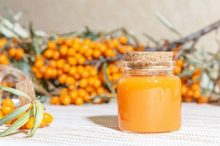 Cosmetology, traditional alternative medicine, herbal medicine, natural sea buckthorn vegetable oil in a glass jar on a table background, healthy juice, branches with a harvest of fresh ripe berries 版權商用圖片