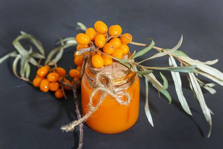 Cosmetology, traditional alternative medicine, herbal medicine, natural herbal cosmetics, sea buckthorn oil in a glass jar on a black background, healthy juice from the harvested autumn crop