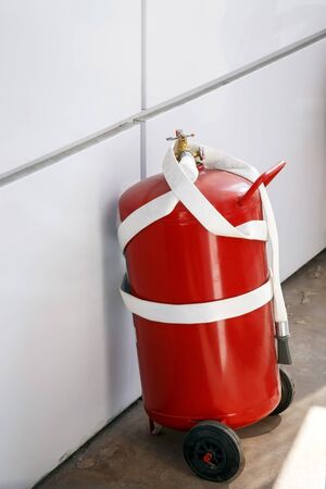 Fire extinguisher near the wall, fire extinguishing equipment and tools, safety measures at gas stations, fire hazard prevention, danger 写真素材