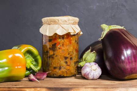 Homemade production canning, canned stewed vegetable puree caviar stewed with eggplant and pepper and garlic in a glass jar on a wooden background in a rustic style. Home provision