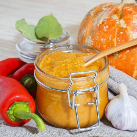 Vegetable caviar, diet puree of pumpkin and zucchini bright orange with pepper, garlic and spices in a glass jar. Vegetarian food, healthy nutrition. Canning homemade crop