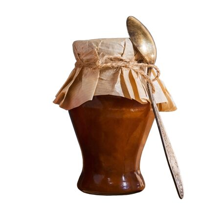 Fruit jam in a closed glass jar with a spoon from peaches apricot apples isolate on a white background. Home canning of summer crops and harvesting