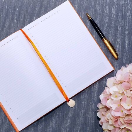 Flatlay with mockup. Notepad clean with a blank page for writing text, pen, pink hydrangea flowers on a gray background