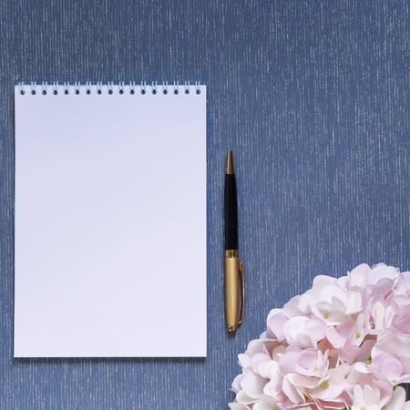 Flatlay with mockup. Notepad clean with a blank page for writing text, pen, pink hydrangea flowers on a blue background