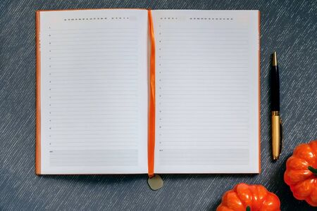 Autumn flatlay with mockup. Blank notebook with blank page, pen, orange pumpkins, Halloween routine on gray-blue background