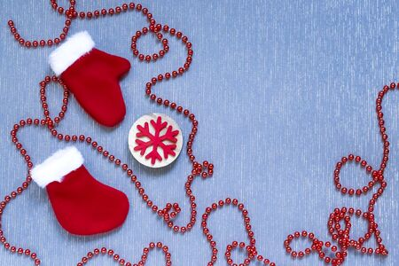 New Year, Christmas background flat lay. Stitched holiday toys, sock, mittens, wooden snowflake and decorative red garland on a blue surface with a copy-space fabric texture 写真素材