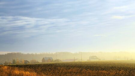 Autumn rural landscape. Village houses in the fog at dawn in a yellow golden field in the sunshine on a warm October day early in the morning against a cloudy blue sky