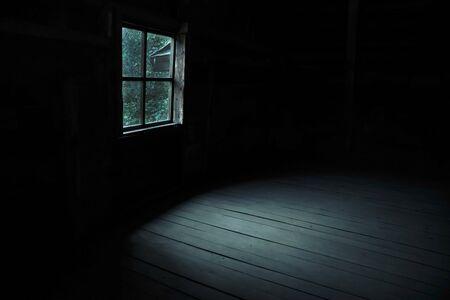 Fondo abstracto de terror para halloween. Lúgubre y aterradora ventana terrible con luz y sombras fantasmales en una habitación oscura y negra en el ático, pasillo o sótano de una casa abandonada en el bosque