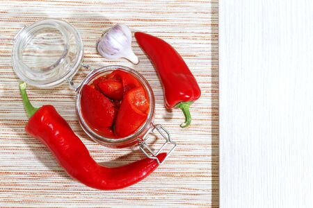 Recipe for baked home-canned bell peppers with garlic in a jar with mockup and copy space. Vetarian healthy food, healthy nutrition, homemade winter preparations