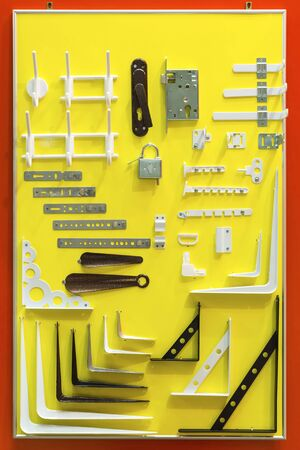 Showcase in the store household goods. Various metal products on a yellow advertising stand to display the range: key products, door hinges, steel hangers, door lock, shoehorn