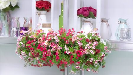 Home floral decor, details of a cozy interior. Artificial bright beautiful summer and spring multi-colored decorative flowers in pink shades and tones on a shelf with various elegant ceramic and glass 写真素材