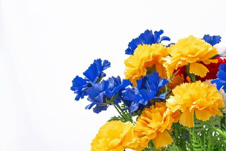 Floral multicolored bright decorative white background with mine space. Bouquet of blue, yellow, orange blooming buds of an artificial carnation flower, empty blank for congratulation text Standard-Bild - 133952121