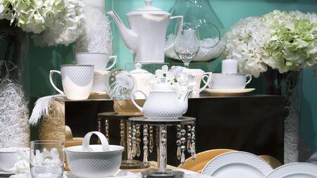 Detale i elementy dekoracji nakrycia stołu, dekoracja świąteczna kolacji w restauracji na uroczystość. Eleganckie porcelanowe naczynia ceramiczne, piękne oryginalne talerze, filiżanki do herbaty w sklepie prezentacyjnym
