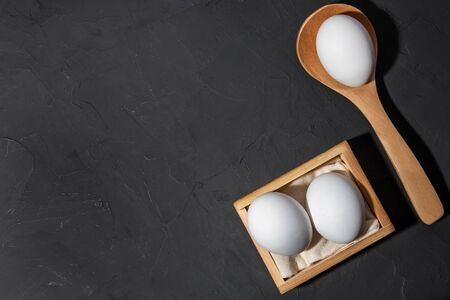 White chicken eggs, black background with copy space. Food and products containing vitamins, proteins, amino acids, choline, lecithin, cholesterol, calcium, potassium, phosphorus, magnesium, iodine