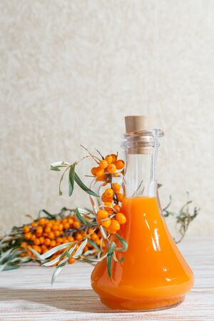 Vegetarian food, healthy nutrition, preserving the harvest of homemade ripe juicy sea-buckthorn, preparing fresh healthy vitamin drink and healing broth. Bottle juice and branches orange sea buckthorn Banque d'images