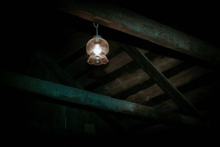 Mystical horror scary garret background to halloween. Old antique dirty wooden ceiling with beams and a lamp in the darkness in a mysterious paranormal frightening basement or attic with black shadow