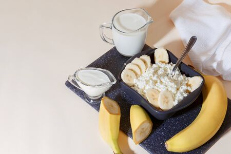 Food, balanced nutrition, healthy diet protein breakfast made from dairy and fruit. Fresh calcium source of homemade cottage cheese in a bowl with sliced banana milk cream sour cream and yogurt