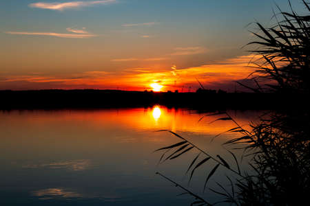 Bright beautiful red orange sunset with reflection in the evening over the horizon above the water on the shore of the pond, fishing, outdoor activities, tourism, nature of Russia in the Saratov region Reklamní fotografie