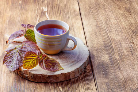 Morning evening relaxing warming medicinal aromatic tea from raspberry leaves in a cup anti-inflammatory antipyretic sedative, flat layout on natural wooden background