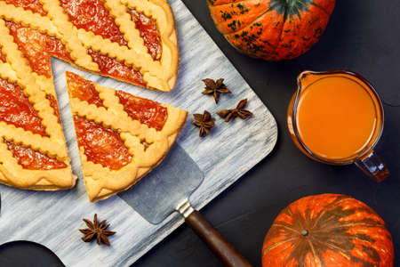 Spicy Holiday Pie Pumpkin Jam with cut Slice, Food Sweet Dessert Homemade Tart with Vegetable Juice Flat lay on Black Concrete Background on Table