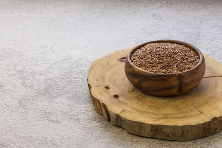 Flax seeds in a wooden bowl on a concrete background, a dietary cereal ingredient for granola that reduces cholesterol, a source of omega-3, vitamins B and C, iodine, phosphorus, potassium, magnesium.