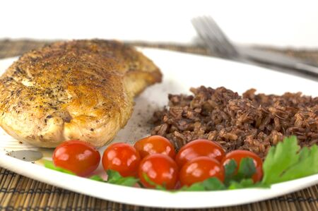 Plate with roast turkey with brown and red rice and whole cherry tomatoes