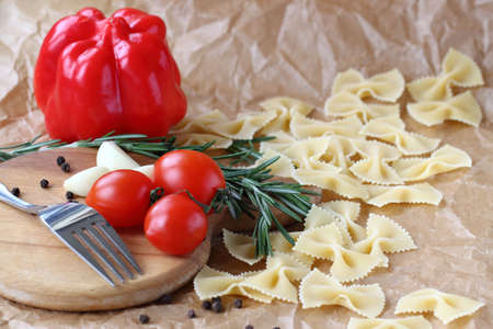 red peppers: Raw farfalle pasta with cherry tomatoes and red peppers on a light background Stock Photo