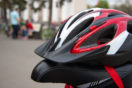 helmet seat: Cycling helmet on a bicycle seat closeup in summer park Stock Photo