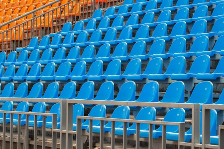 orange chairs: Rows of blue and orange chairs on a soccer stadium