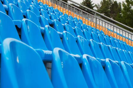 orange chairs: Rows of empty blue and orange chairs on a soccer stadium