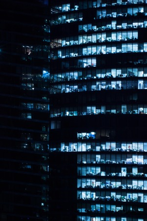 civilized: Windows of business office in a tall building at night in dark tones. Blur in blue tones, vertical Stock Photo