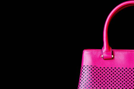 fuchsia color: Large part the perforated handbag for women of color of bright fuchsia , texture close-up, dark background. With your place for the text.