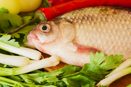 crucian: Crucian fish close up ready for cooking on the kitchen table with vegetables Stock Photo