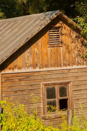 Alte verlassene Holzhaus mit verwitterten zerbrochenen Fenster auf einem ruhigen Sommertag Standard-Bild