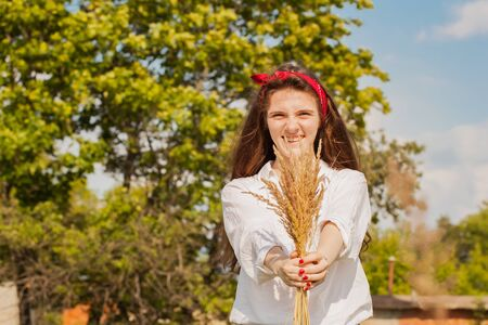 Young smiling girl with beautiful long hair offering a ears bouquet for us, focus on it. Summer sunny day