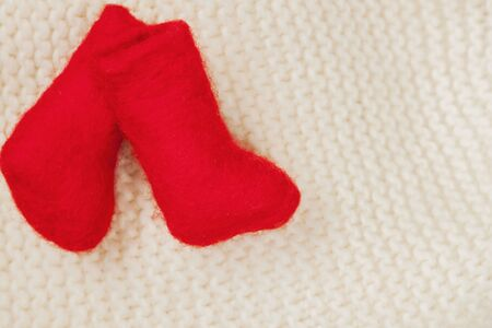 valenki: Pair Christmas red miniature felt boots for decoration on a white knitted cap. With place for your text, for background use.