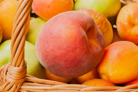 hormonal: Bright peach close-up lying in wicker basket with other summer fruit. Low Calorie, for digestive tract, healthy heart , from wrinkles, excess salt from body, restore hormonal balance, male strength Stock Photo