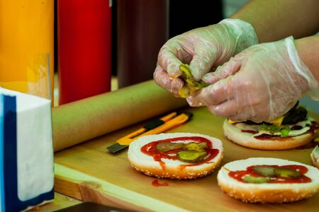 Closeup of mans hands, different kinds of burgers cooking on a BBQ-party Stock Photo
