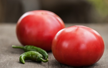 encountered: Two fresh home-grown tomatoes and spicy green chili peppers on a rustic wooden kitchen table. Two commonly encountered ingredient in many dishes and sauces. Stock Photo