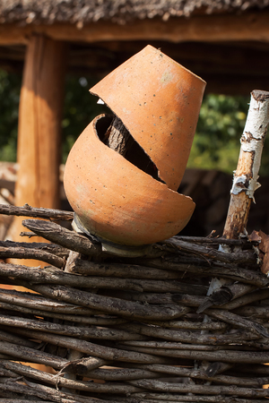 Summer day , Rural scene. Old broken clay Jug close up at wattle fence Stock Photo