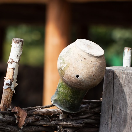 Village,rustic wattle fence, old clay jug. Rustic scene Stock Photo