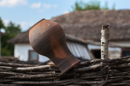 cheapness: Old clay Jug on palisade wicker fence, rustic style, rural scenery Stock Photo