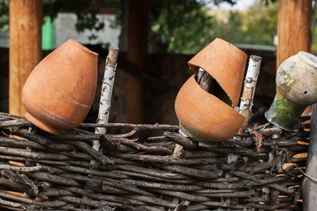 cheapness: Village, rustic palisade wattle fence, old clay pots . Rural scene Stock Photo